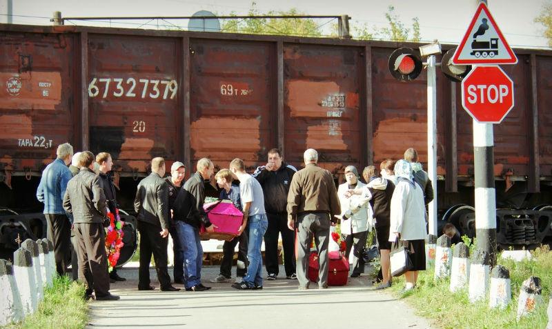 Жители подмосковного города с гробами пролезают под поездом, чтобы похоронить родных